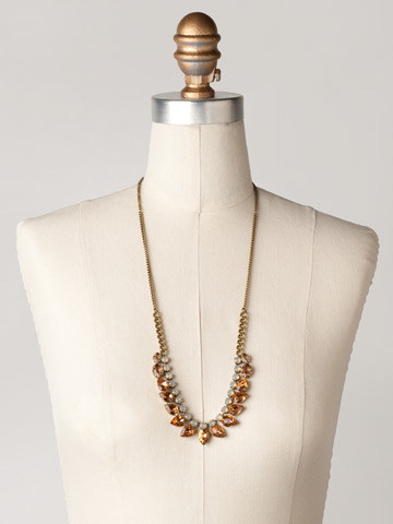 Round and Pear Crystal Line Necklace in Antique Gold-tone Desert Sun displayed on a necklace bust