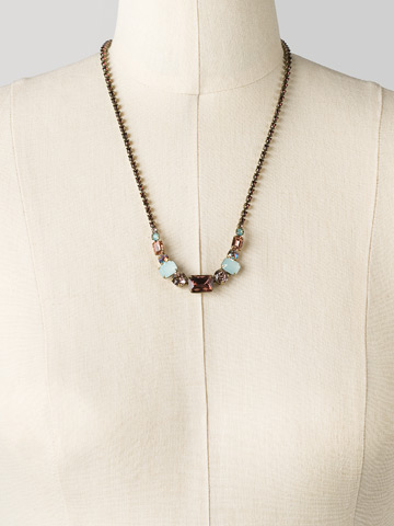 Graduated Geometric Crystal Line Necklace in Antique Gold-tone Sangria displayed on a necklace bust