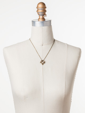 Embroidered Trifecta Pendant in Antique Gold-tone Neutral Territory displayed on a necklace bust