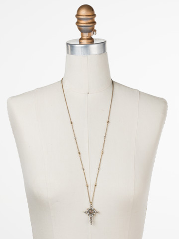 Celestial Cross Pendant in Antique Gold-tone White Magnolia displayed on a necklace bust