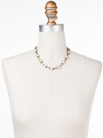 Mini Eyelet Line Necklace in Antique Gold-tone Pearl Luster displayed on a necklace bust