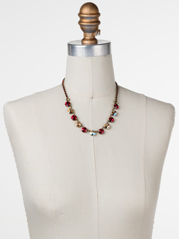 Simply Sophisticated Line Necklace in Antique Gold-tone Go Garnet displayed on a necklace bust