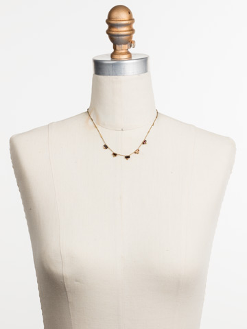 Shine and Dash Necklace in Antique Gold-tone Mighty Maroon displayed on a necklace bust