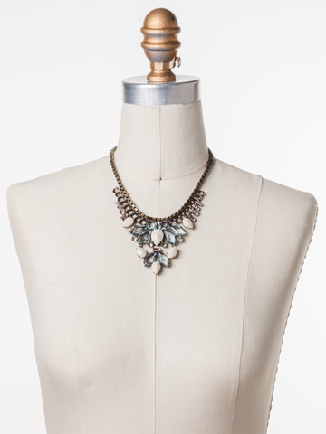 Cascading Crystals Statement Necklace in Antique Gold-tone Coastal Mist displayed on a necklace bust