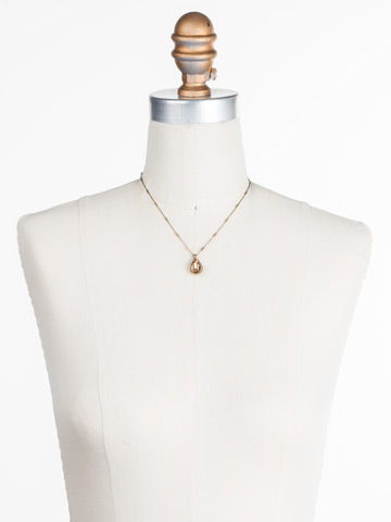 Simply Adorned Pendant in Antique Gold-tone Neutral Territory displayed on a necklace bust
