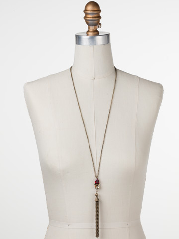 Timeless Tassel Necklace in Antique Gold-tone Go Garnet displayed on a necklace bust
