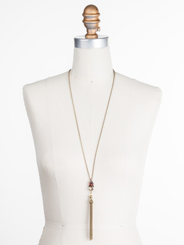 Timeless Tassel Necklace in Antique Gold-tone Mighty Maroon displayed on a necklace bust