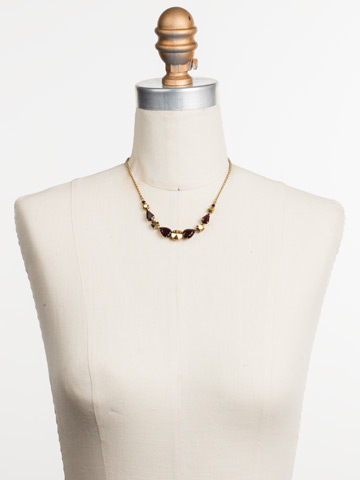 Polished Pear Necklace in Antique Gold-tone Mighty Maroon displayed on a necklace bust