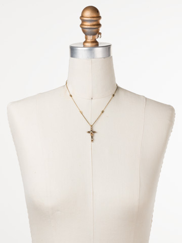 Delicate Sliding Cross Pendant Necklace in Antique Gold-tone Sandstone displayed on a necklace bust