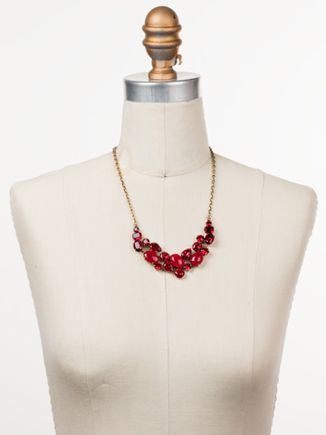Forget-Me-Not Necklace in Antique Gold-tone Sansa Red displayed on a necklace bust