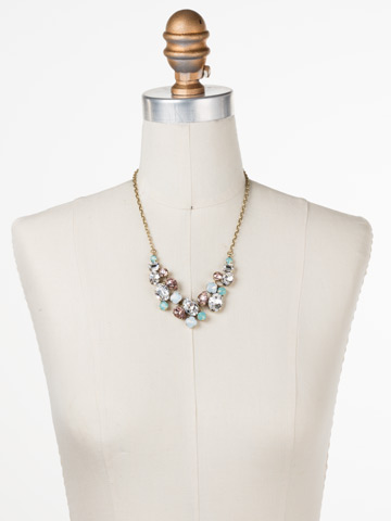Forget-Me-Not Necklace in Antique Gold-tone White Magnolia displayed on a necklace bust
