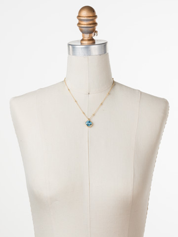 Cushion-Cut Solitaire Necklace in Bright Gold-tone Aquamarine displayed on a necklace bust