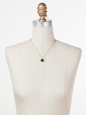 Cushion-Cut Solitaire Necklace in Bright Gold-tone Emerald displayed on a necklace bust