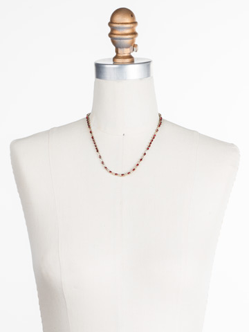 The Skinny Necklace in Antique Gold-tone Go Garnet displayed on a necklace bust