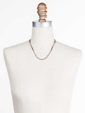 The Skinny Necklace in Antique Gold-tone Mighty Maroon displayed on a necklace bust