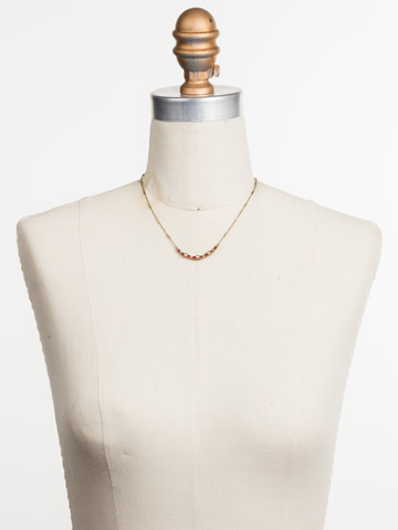 The Skinny Mini Necklace in Antique Gold-tone Go Garnet displayed on a necklace bust