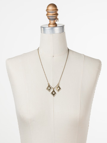 Love Tri-Angle Necklace in Antique Gold-tone Crystal displayed on a necklace bust