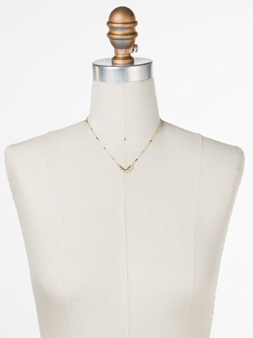 Jagged Chevron Necklace in Bright Gold-tone Crystal displayed on a necklace bust