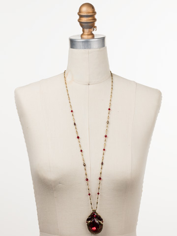 Armeria Necklace in Antique Gold-tone Sansa Red displayed on a necklace bust