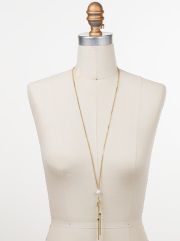 Raffaella Tassel Necklace in Bright Gold-tone Polished Pearl displayed on a necklace bust