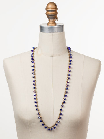 Marjorie Long Strand Necklace in Antique Gold-tone Game of Jewel Tones displayed on a necklace bust