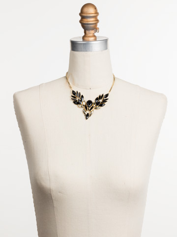 Melisandre Bib Necklace in Bright Gold-tone Jet displayed on a necklace bust