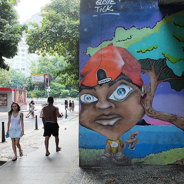People passing by a mural by @Gloye and @LeandroTick in Copacabana in Rio de Janeiro, Brazil. Guy with spray can!