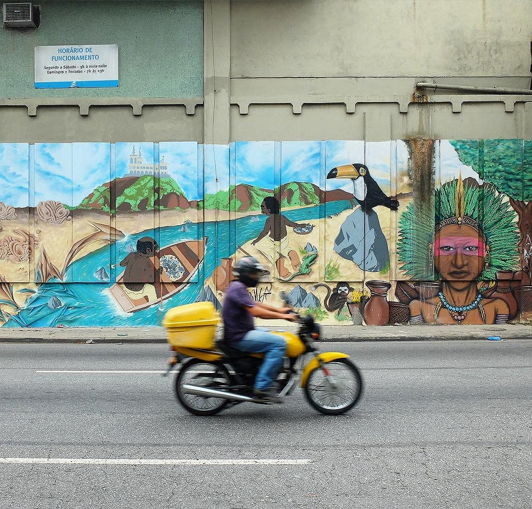 Man riding a motorcycle past a mural by @FaelTujaviu and *please tag the other artists* for @Metro_Rio in Inhaúma in Rio de Janeiro, Brazil. The history of Inhaúma!