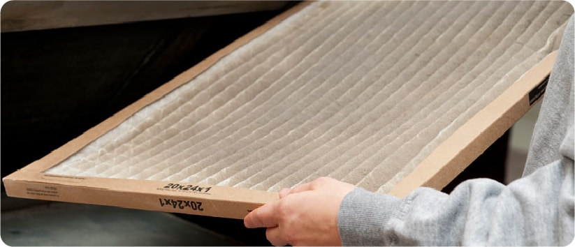 person replacing their furnace filter to keep the air cleaner