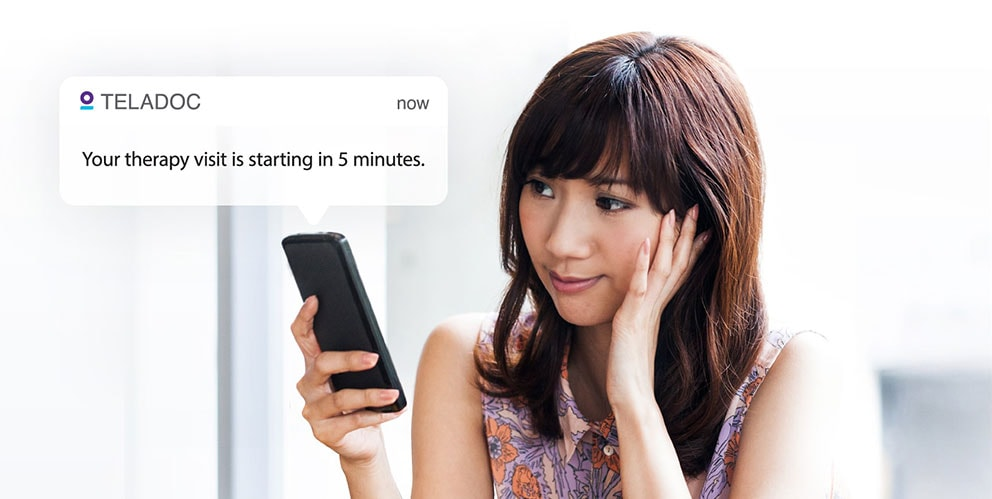 Woman looking at a push notification on her smartphone notifying her that her Teladoc mental health visit is starting in 5 minutes.