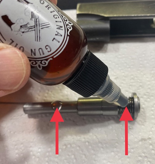 Apply one drop at each arrow on the recoil spring assembly