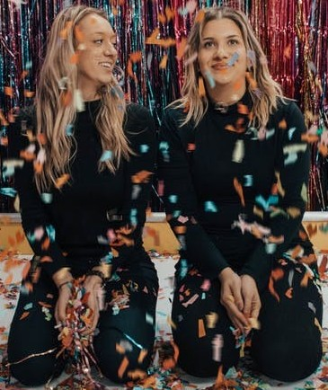 Two Women Wearing Black Playing In Confetti
