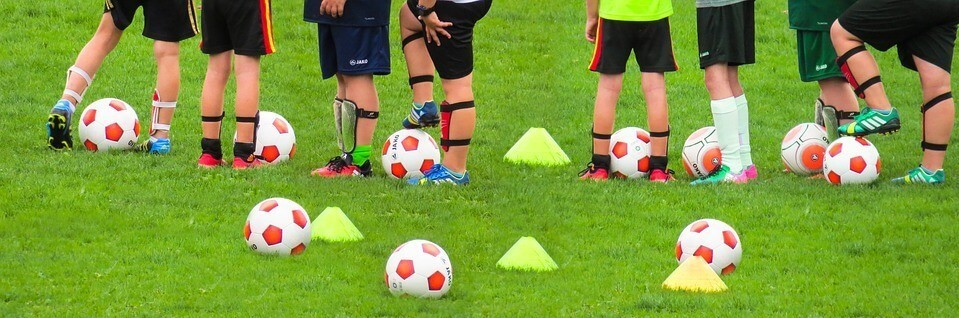 Soccer players standing around with training cones and soccer balls on the ground