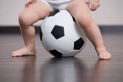 barefoot toddler sitting on a soccer ball
