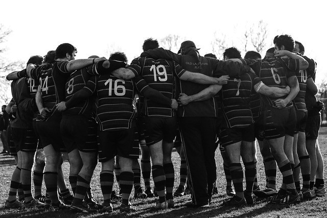 Black and white image of a rugby team in a huddle