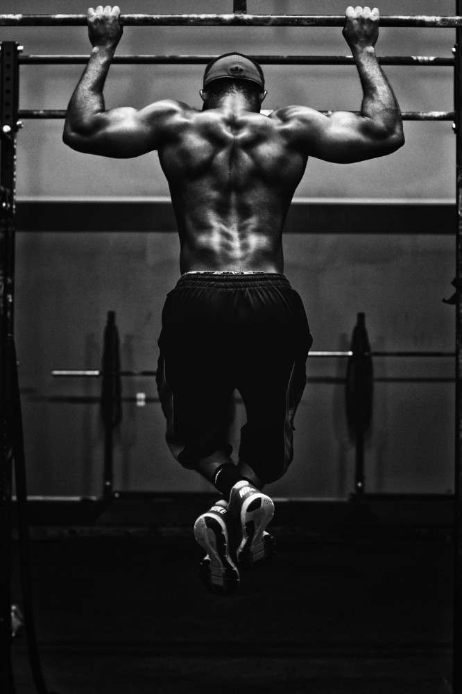 Shirtless man facing away from the camera doing pull ups on a bar above his head