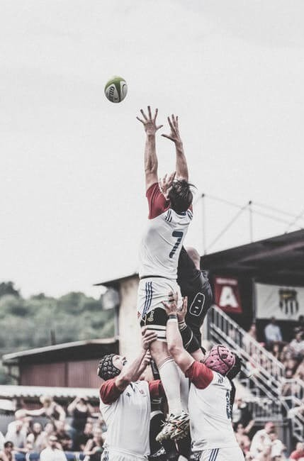a rugby player being lifted in the air by his team mates to catch a rugby ball in the line-out