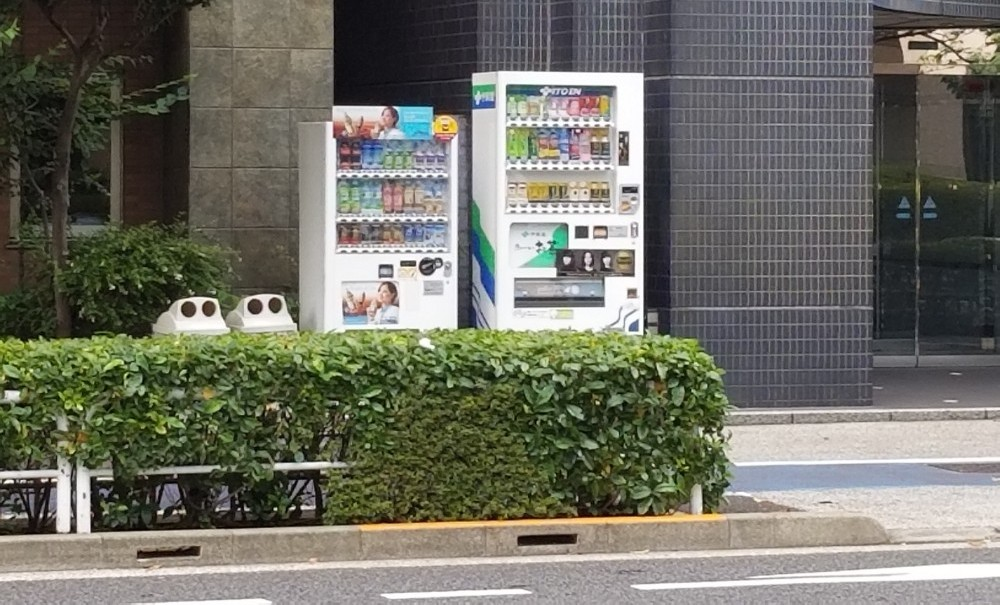 Japanese vending machine on the street with recycle bins