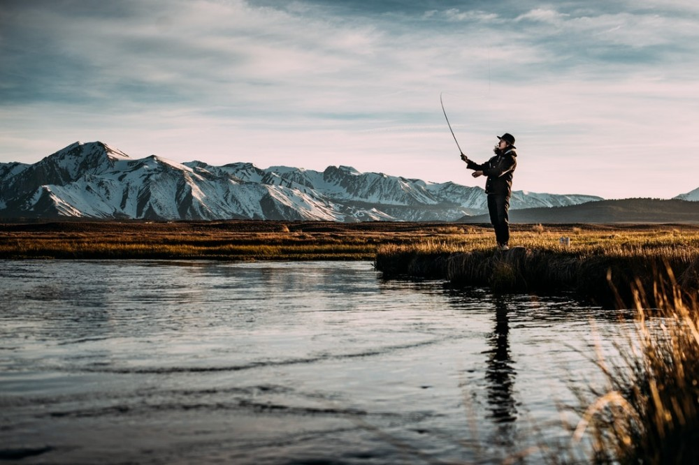 man fishing on water with spinning rod with blue sky and mountains in the background.