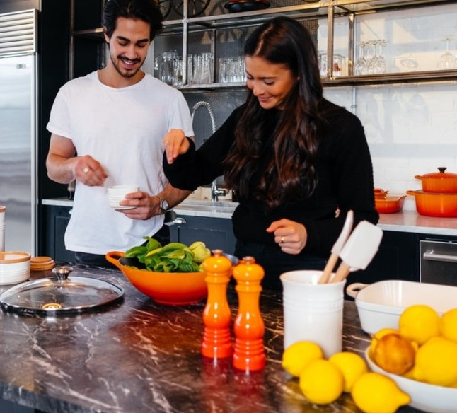 woman showing man how to make a salad