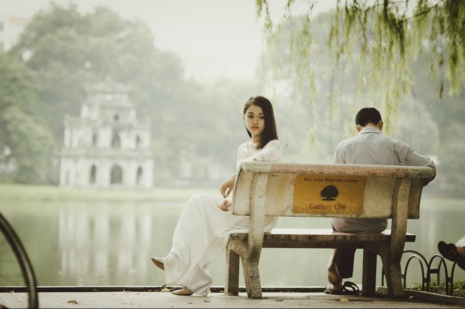 unhappy man and woman on a bench beside a lake.