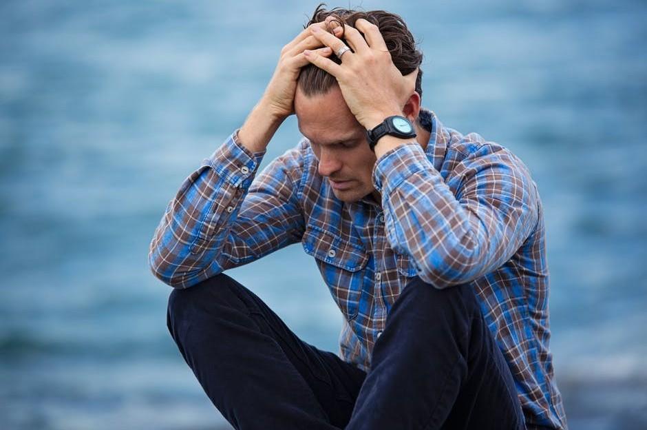 man in despair beside the water