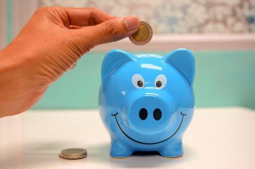 Putting coin in a piggy bank