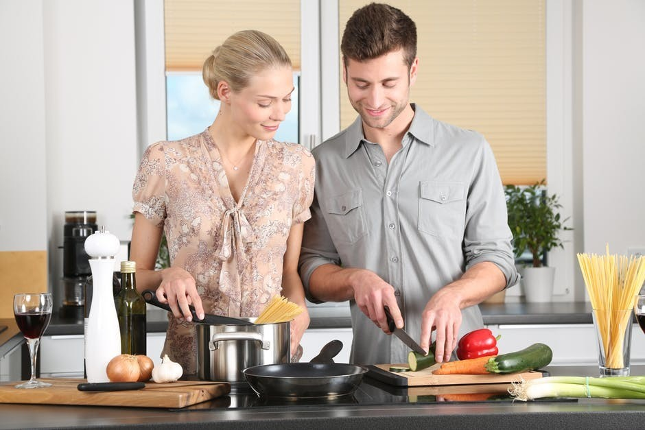 couple in kitchen cutting vegetables