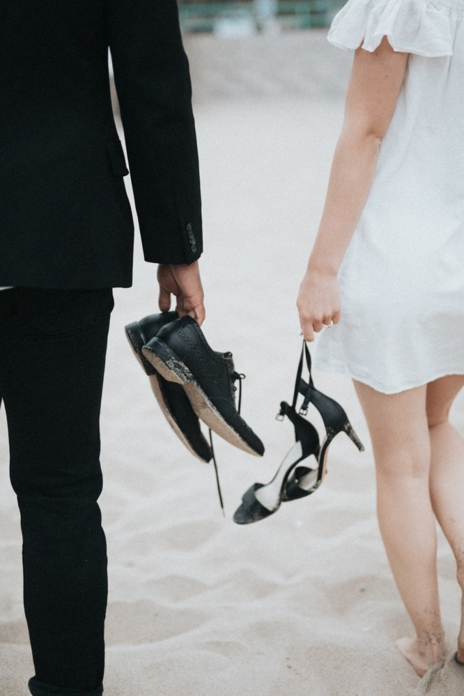 bride and groom holding shoes on beach