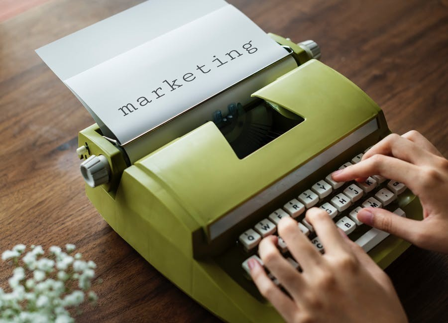 girl typing 'marketing' on green typewriter
