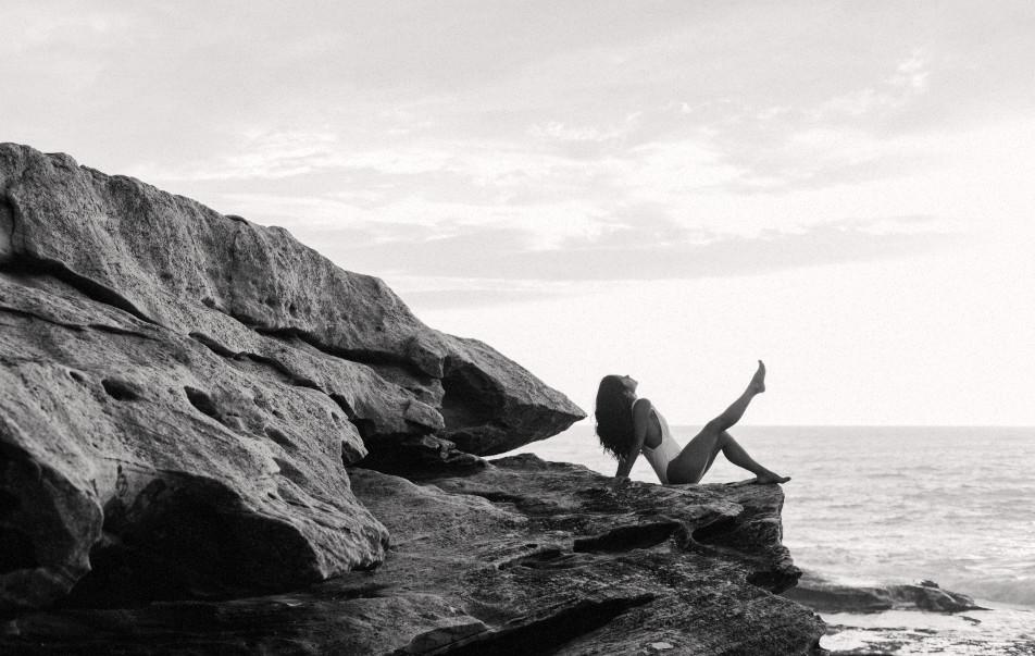 woman on rock by ocean