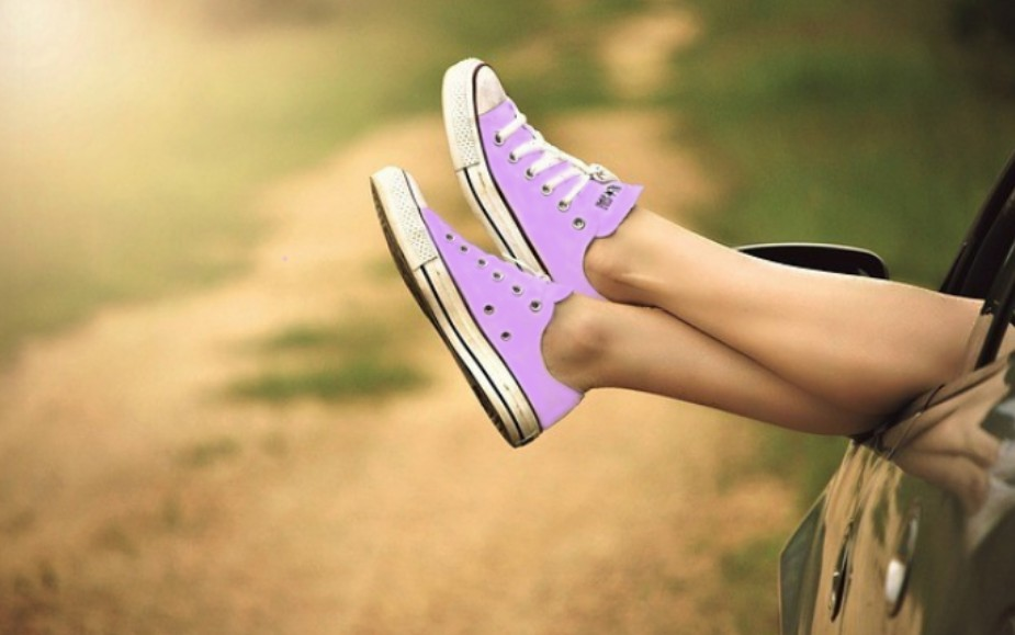 purple sneaker on crossed ankles