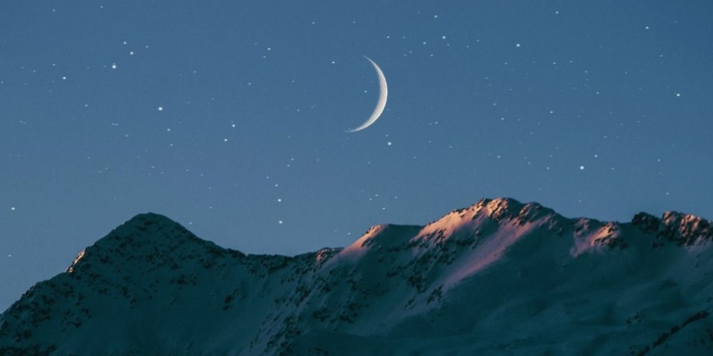 crescent moon over mountains