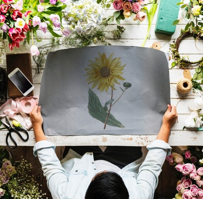 Person holding a picture of a flower